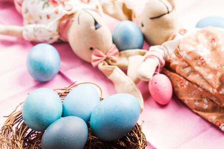 Pink easter holiday concept with bunny and blue colored hard boiled eggs in a wicker nest