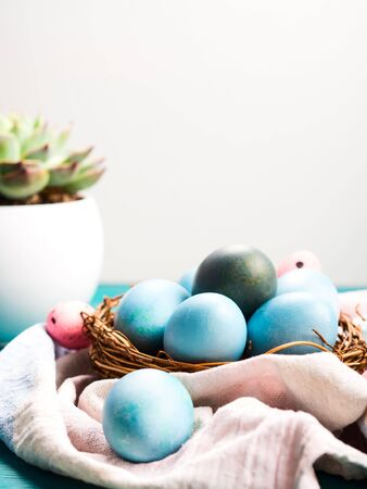 Easter hard boiled blue eggs in nest on green wooden table. Traditional holiday snack Stock Photo