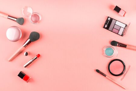 Make up products and brushes on pink background. Beauty items colorful fashion flat lay 스톡 콘텐츠