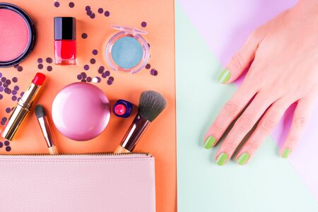Make up products and brushes with confetti on orange and green geometrical background. Female hand with mint manicure. Beauty concept