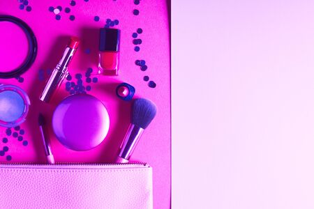 Make up products and brushes on pink and purple neon background. Beauty items colorful fashion flat lay with copy space. Duotone