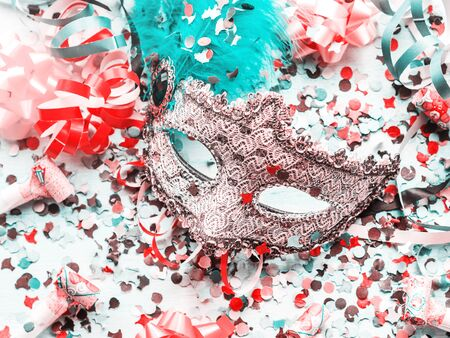 Colorful cranival Mardi gras background with masquerade carnival mask and confetti, streamers, bows. Party items.