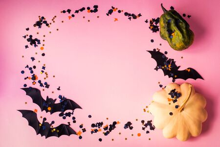 Halloween pumpkin and black bat decor with dark color and golden confetti on trendy pink background. Flat lay mock up frame