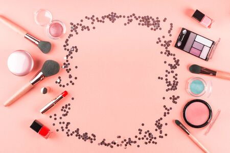 Make up products on pink coral with sparkling confetti frame. Beauty items colorful fashion flat lay background