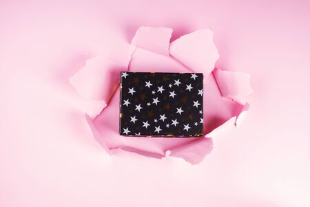 Black gift box in a hole on pink background. Black Friday or Christmas surprise concept 스톡 콘텐츠