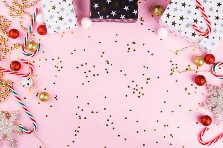 Christmas ornaments, baubles and candy canes with golden stars confetti on pink background. Festive flat lay frame