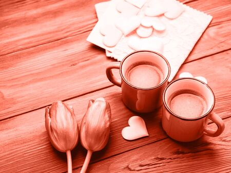 Two cups of coffee, hearts and tulip flowers. Valentines day concept on wooden background. Pink coral tone