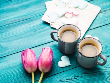 Two cups of coffee, hearts and tulip flowers. Valentines day concept on dark wooden emerald green background