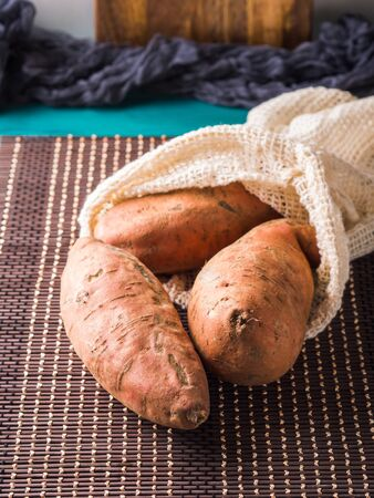 Sweet potato tubers in a reusable cotton shopping mesh bag on dark background. Zero waste, plastic free concept. Ugly vegetables