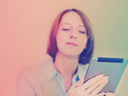 Young woman in shirt using her tablet ans smiling. Duotone gradient tone.