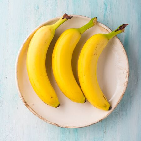 Three bananas on a plate on green turquoise background. Healthy lifestyle concept Zdjęcie Seryjne