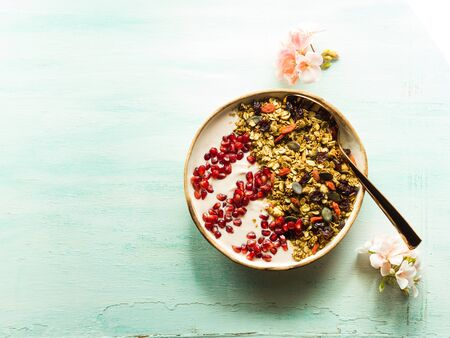 Home made smoothie bowl with yogurt and pomegranate with granola of dried fruit, seeds and nuts. Spring mood with pink flowers on pastel background. Simple healthy breakfast