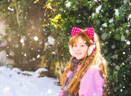 Portrait of little redhead girl with snow and trees in the background. Enjoying winter holidays Zdjęcie Seryjne