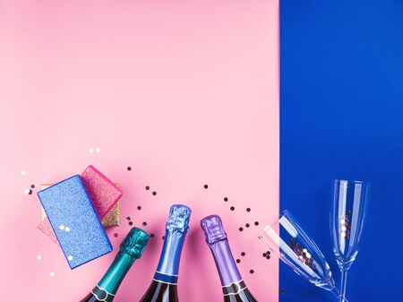 Champagne bottle, gifts and flutes on pink and classic blue background with sparkling confetti. Celebrating new year, christmas, valentines day concept festive flat lay. Anniversary, birthday party