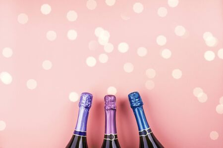 Three champagne bottles and bokeh lights on pink color background. Celebrating new year, christmas, valentines day festive flat lay. Anniversary, birthday party concept Zdjęcie Seryjne