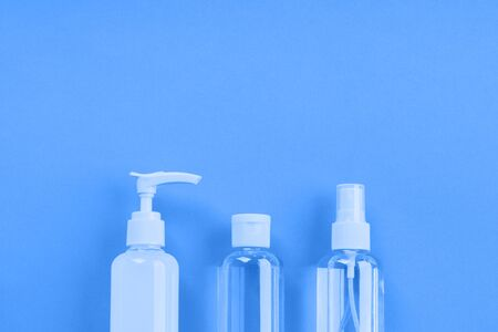 Generic beauty products on classic blue background. Summer travel kit or sun protection concept.