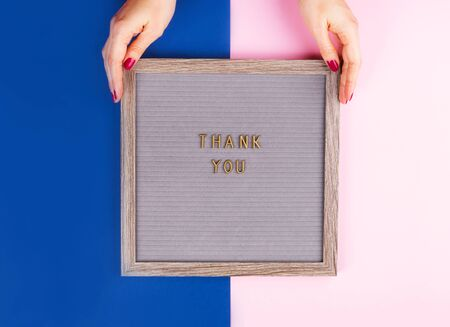 Thank you text composed on wooden board with letters on colorful classic blue and pink background. Female hands holding the board. International Thank-You day concept