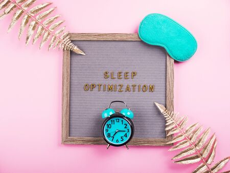 Sleep optimization text composed on wooden letter board with green sleeping mask, alarm clock, golden branches. Better healthy sleep tips concept Zdjęcie Seryjne