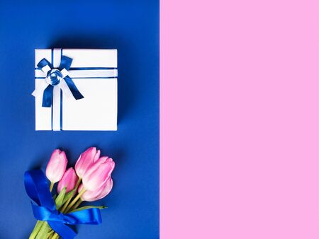 Elegant gift box with ribbon and beautiful tulips on pink and classic blue 2020 color split duotone trendy backdrop. Festive flat lay for greeting card. Mothers day, Womans day, Valentine