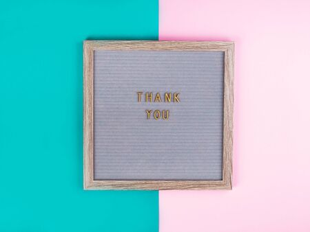 Thank you text composed on wooden board with letters on colorful tuquoise and pink background. International Thank-You day concept