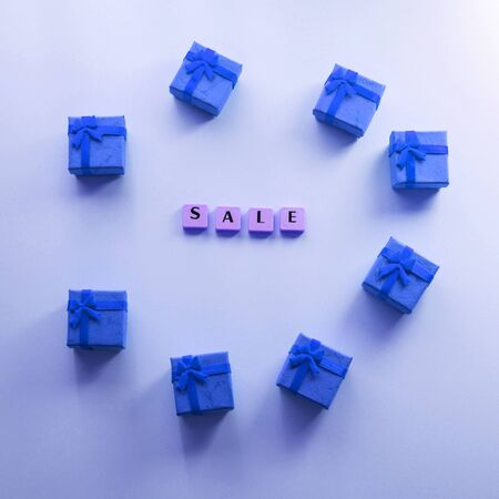 Sale word composed with plastic tiles on blue background with small classic blue gift boxes. Discount period concept flat lay