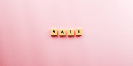 Sale word composed with plastic tiles on pink background. Discount period concept flat lay