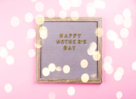 Mothers day greetings on wooden letter board on pink trendy monochrome backdrop. Copy space flat lay with magic bokeh lights