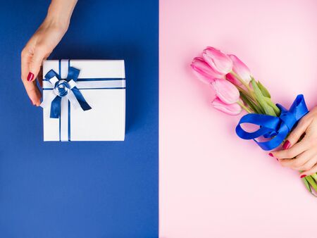 Female hands with red manicure holding beautiful tulips and gift box with ribbon on pink and classic blue 2020 color split duotone trendy backdrop. Festive flat lay for greeting card or other projects