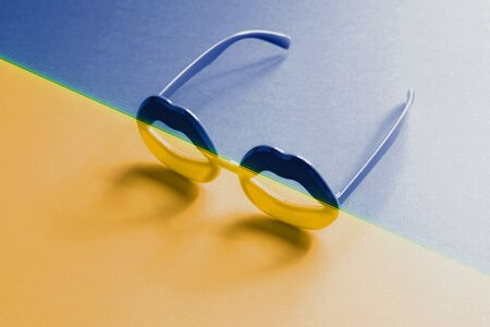 Lip shape glasses in yellow blue duotone gradient with glitch.