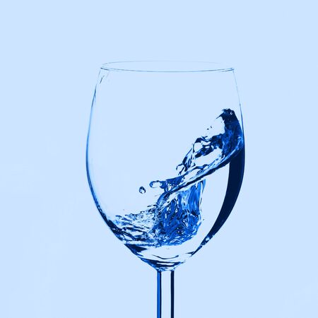 Half empty glass with water splashes in motion. Classic blue color of 2020 Zdjęcie Seryjne