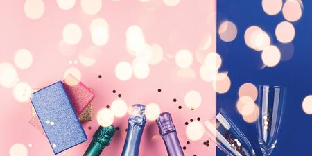 Champagne bottle, gifts and flutes on pink and classic blue background, sparkling confetti and holiday lights. Celebrating new year, christmas, valentine festive flat lay. Anniversary, birthday banner