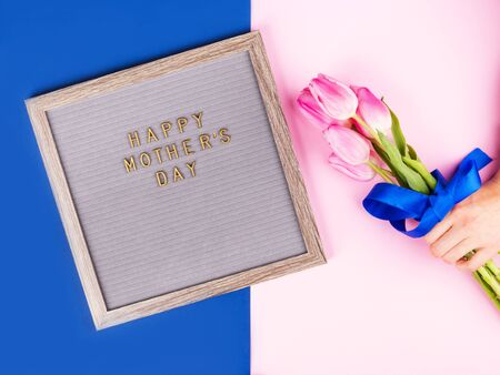 Mothers day greetings on letter board and female hands with red manicure holding beautiful tulips on pink and classic blue trendy split backdrop. Stock Photo