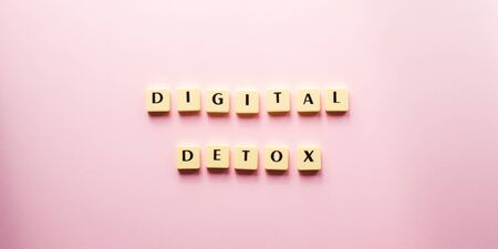 Digital detox text in tiles. Flat lay concept of tech escape on pink background