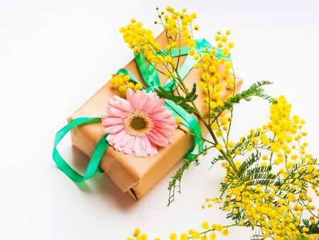 Womans day concept. Gift box wrapped in craft paper with mimosa flowers and pink gerbera
