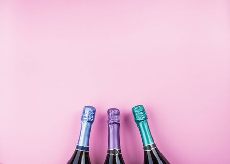 Three champagne bottles in pastel colors on pink background. Celebrating new year, christmas festive flat lay. Anniversary, birthday party concept