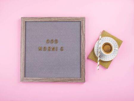 Good morning phrase with missing letters on letter board with coffee espresso cup and golden agenda or diary with pencil over millennial pink background. Trendy art flat lay Zdjęcie Seryjne