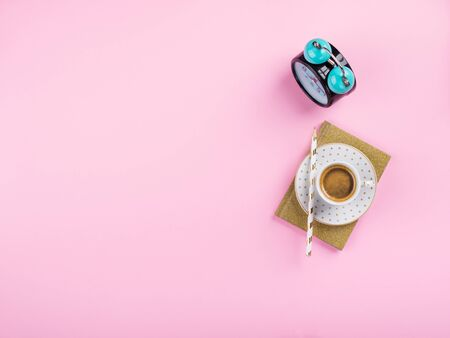 Good morning concept with coffee espresso cup and golden agenda or diary with pencil over millennial pink background. Trendy flat lay with copy space