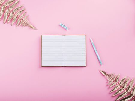 Golden tropical plant branches frame and open notebook on white pages with pen on pink millennial backdrop. Trendy flat lay and mock up for writing