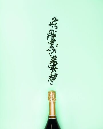 Champagne bottle with confetti flow as bubbles on aqua mint green background. Celebrating new year flat lay. Anniversary, birthday party concept