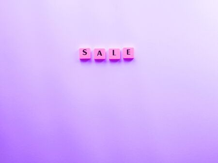 Sale word composed with plastic tiles on purple background. Discount period concept flat lay