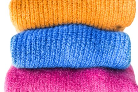 Pile of cozy winter woolen sweaters isolated on white. Vibrant colors, womans fashion. Color match with classic blue tone clothes