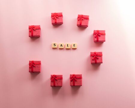 Sale word composed with plastic tiles on pink background with small red gift boxes. Discount period concept flat lay