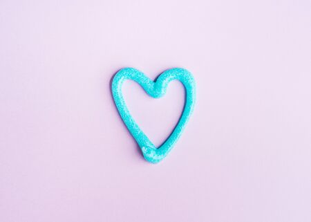 Heart symbol made of turquoise toothpaste on pink background. Flat lay dental hygiene concept