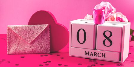 Celebrating womens day still life on pink and red background. March, 8 on wooden calendar, envelope with greeting card, heart shaped present and flowers. Stock Photo