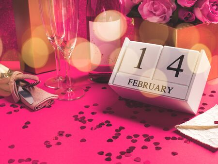 Happy valentines day concept with champagne flutes and red heart confetti, wooden calendar with February, 14 date, envelope, heart shaped gift box, rose flowers. Festive angle shot still life 免版税图像 - 139602767