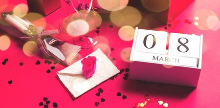 Festive womens day concept with wood calendar and March, 8 date, champagne flute, elegant silverware and red heart confetti, envelope, heart shape gift box, rose flowers. Stock Photo