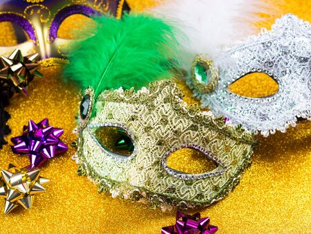 Colorful mardi gras carnival masks on golden glitter background. Festive holiday still life flat lay Stock Photo