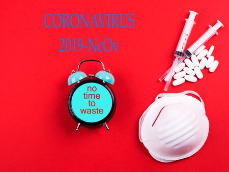 New novel coronavirus 2019-nCoV   Epidemic danger prevention. Vaccine, treatment concept with masks, syringes and antibiotic pills. Clock with text No time to waste. Stop epidemic