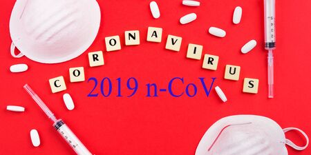 New novel coronavirus 2019-nCoV Epidemic danger prevention. Vaccine, treatment concept with masks, syringes and antibiotic pills and text in letter tiles