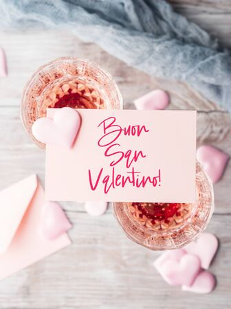 Two stemmed champagne glasses with pink hearts blank paper note card on wooden textured background. Happy valentines day greetings in italian. Greeting card with text